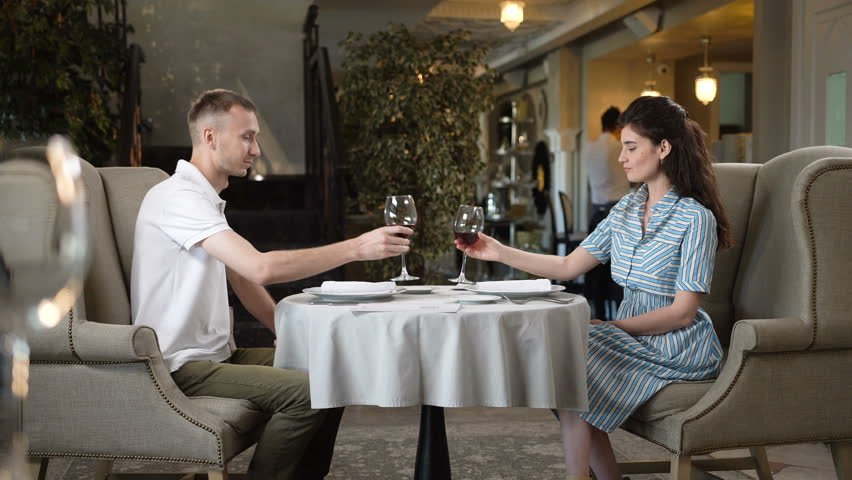 KAZAN, TATARSTAN/RUSSIA - OCTOBER 25 2017: Happy beautiful woman and man lifts up high glasses and taste red wine in modern restaurant on October 25 in Kazan   Shutterstock HD Video #33801235