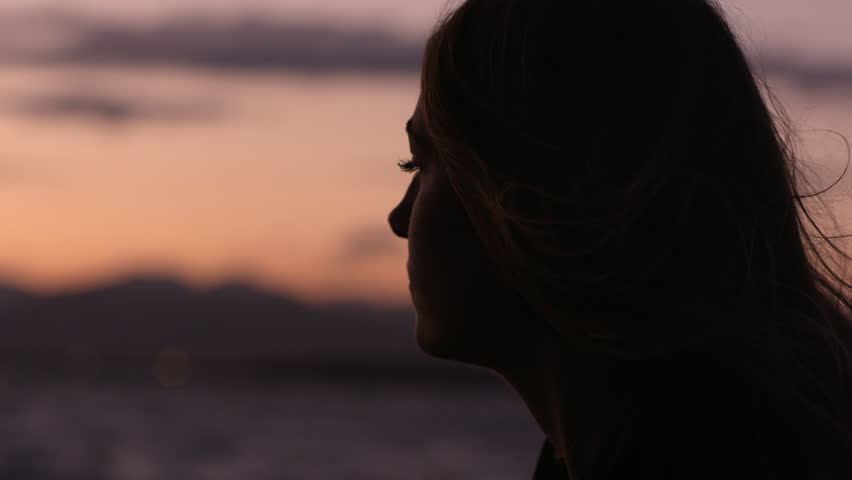 Young woman's face closeup at sunset next to lake. with colorful orange sky.