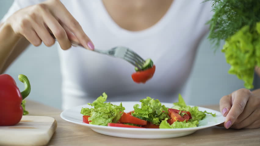 Woman eating vegetable salad, observing diet and counting calories, wellness