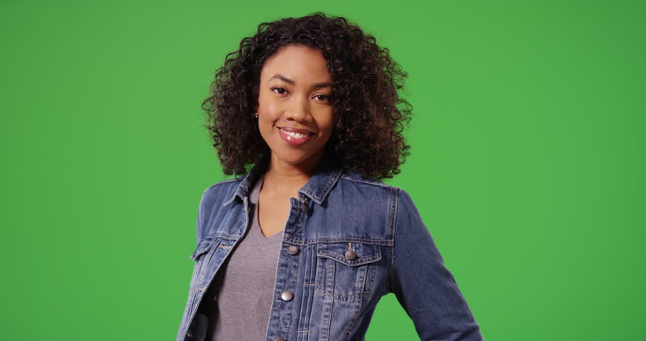 Portrait of happy black woman in jean jacket posing playfully on green screen. Close up of stylish African American Millennial girl smiling and laughing on greenscreen for keying or compositing. 4k