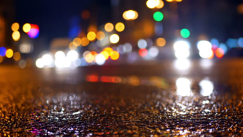 Low shot of puddle whilst it rains with traffic