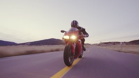 Motorcyclist racing his motorcycle down straight country road going a high speed at sunset with headlights on
