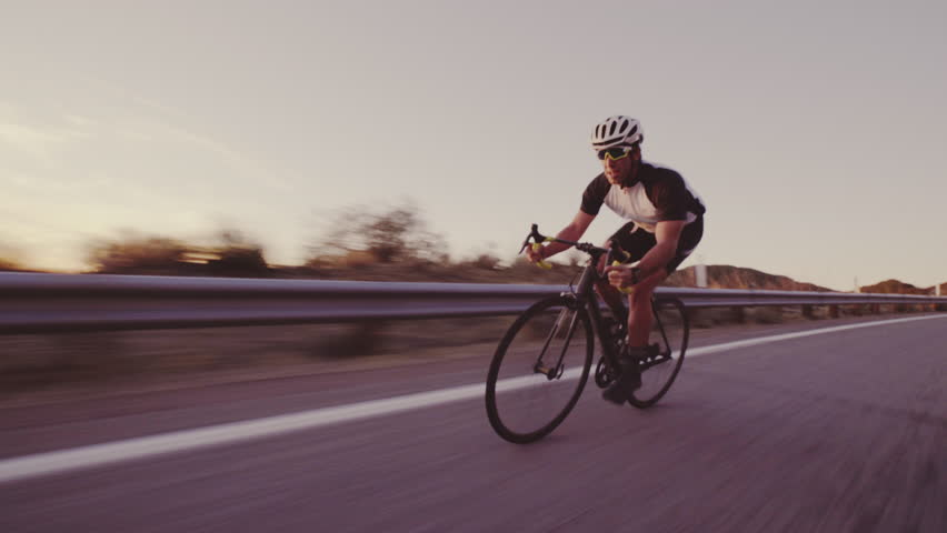 Young Fit Man Cycling On Road Bike Outside At Sunset Racing Downhill | Shutterstock HD Video #33811609