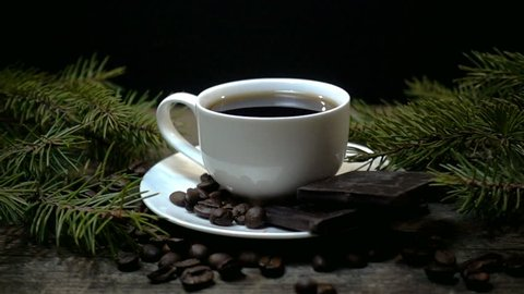 A cup of coffee and falling coffee beans in slow motion on a Christmas background
