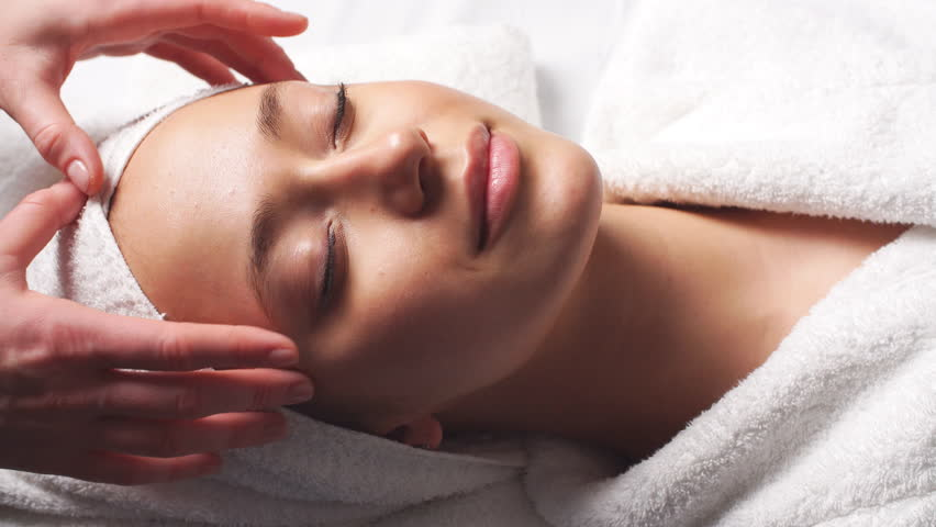 Spa woman facial Massage. Face Massage in beauty spa salon. Female enjoying relaxing face massage in cosmetology spa centre. Body care, skin care, wellness, beauty treatment.