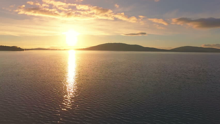 AERIAL: Colorful morning view on huge lake with mountains on the horizon. Beautiful sunrise in wild nature. Environment, peaceful rest, tourism, weekend. | Shutterstock HD Video #33819556