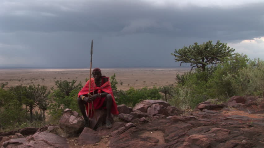Masai Warrior in traditional clothes sitting and singing before the Storm.