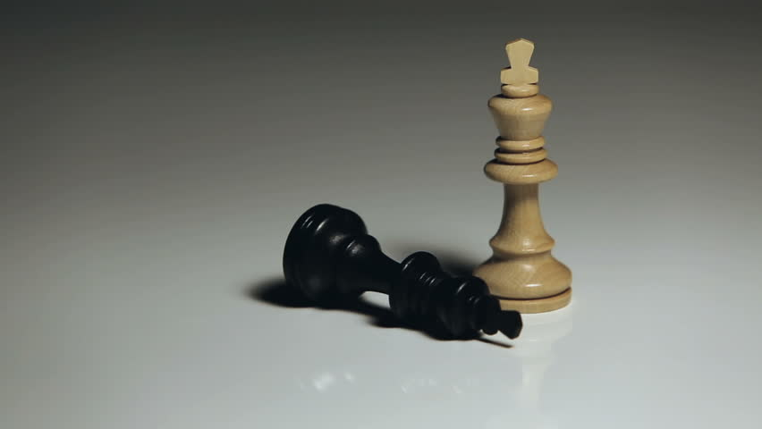 Chess pieces: a hand puts down the black king, while the white king remains standing.    Shutterstock HD Video #33825394