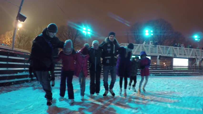 MOSCOW - JUN 15, 2017: Man, woman, two girls and two boys (with model releases) skate in row on ice rink of Gorky Park. During season, ice rink in Gorky Park expects to receive about 1 million people. | Shutterstock HD Video #33844360
