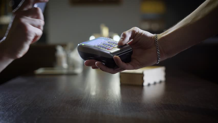 People are using contactless payment by phone in a restaurant, hand with smartphone is touching payment terminal   Shutterstock HD Video #33844702