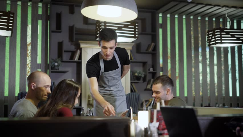 polite waiter is helping to company of friends to choose meals from menu in a restaurant in dinner hour Royalty-Free Stock Footage #33844705