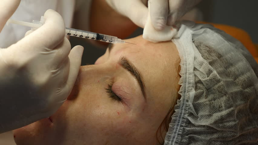 Beauty clinic. Beautician hands in gloves making face aging injection in a female skin. A woman gets beauty facial cosmetology procedure. Botox. collagen injections. Shot in 4k
