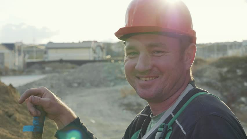 Against the sun portrait of construction worker in helmet with shovel standing near the sand pile. Builder looking at camera and smiling at construction site, slow motion. #33847441