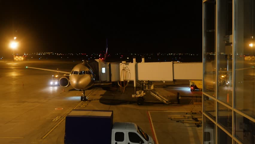 Close view of aircraft fuselage near the entering baggage door, at night. Plane takes passengers. Timelapse