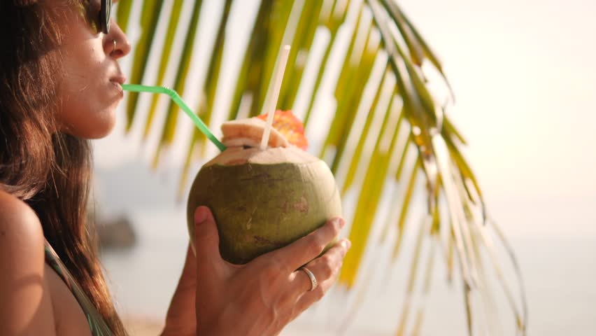 Attractive Mixed Race Young Tourist Hipster Girl Drinking Fresh Thai Coconut Water Cocktail under Palm Tree at Tropical Beach. 4K, Slowmotion. Phuket, Thailand.