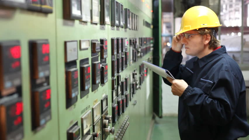 The worker writes the results of measuring devices in the control room at the factory