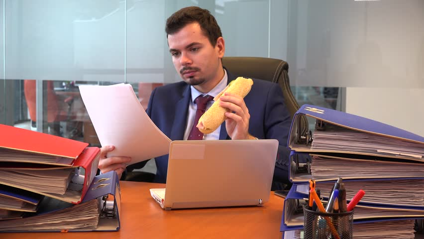 Workaholic formal wear business man manager accountant reading paperwork eating  | Shutterstock HD Video #33903097