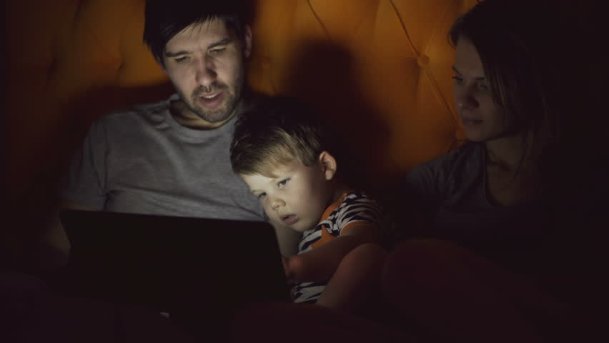 Happy family with little son learning to play tablet computer lying in bed at home in evening #33907279