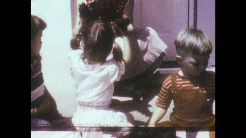 1950s: Girl holds dog up. Puppy lies on stoop as children pet it. Mother dog sits on lawn. Boy sits on lawn and speaks. Dog sits on lawn. Boy laughs and walks away. | Shutterstock HD Video #33908554