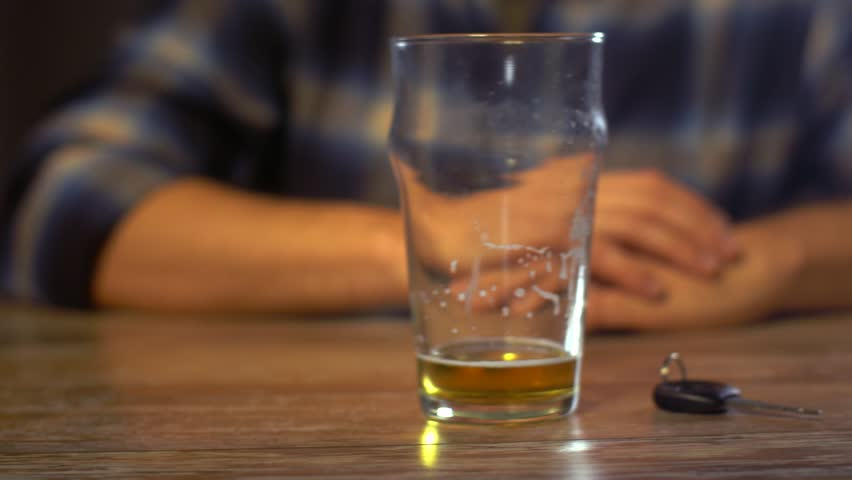 Alcohol abuse, drunk driving and people concept - male driver drinking alcoholic beer at home or bar and taking car key from table