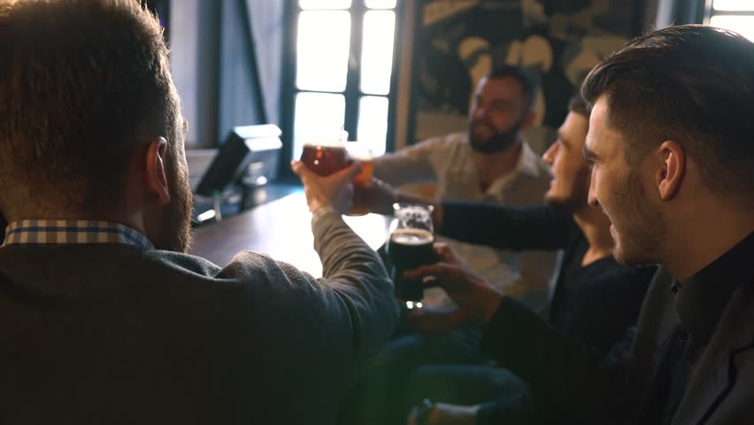 Four happy friends are clicking glasses with the beer sitting at the table in the bar. Close-up photo | Shutterstock HD Video #33919312