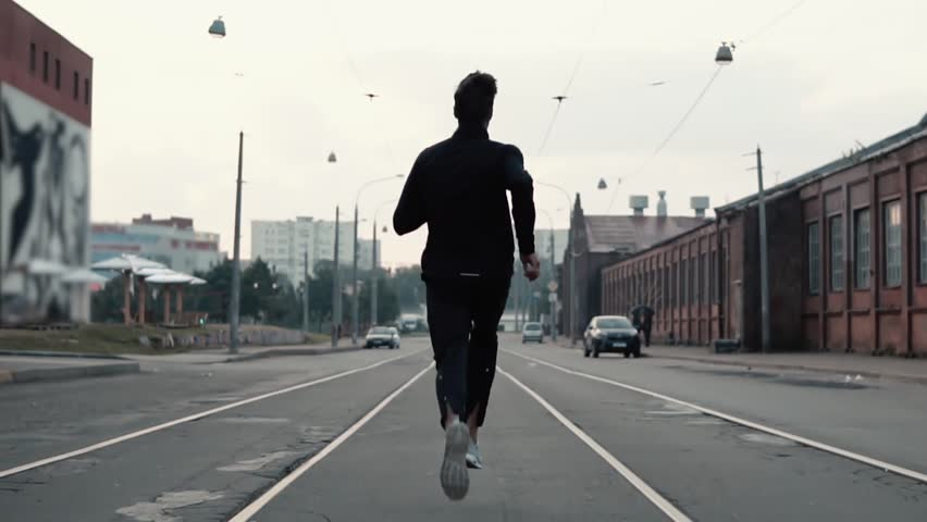 Man running in the middle of the street. Background shot. Slow motion. Abstract concept of individual success and fame. | Shutterstock HD Video #33920146