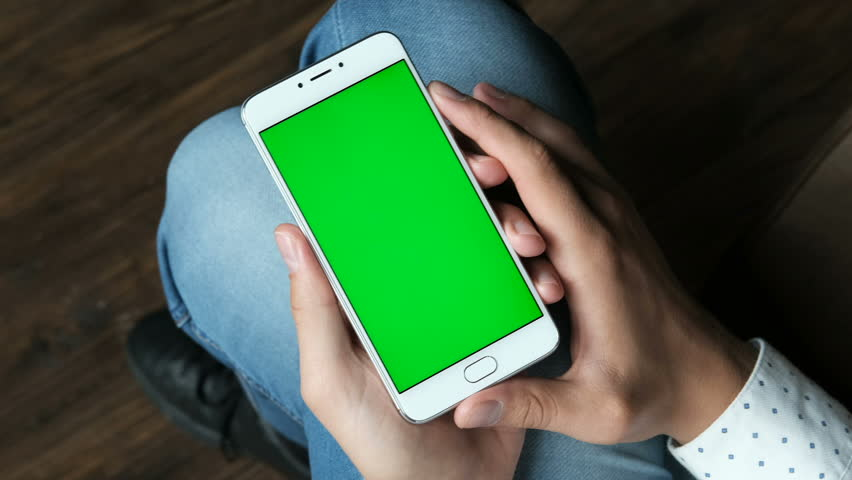 Guy hold cellular portable device with greenscreen chromakey closeup point of view. Human sitting, use handheld cellphone. Relax mood online by reading news, watch video, playing games and surfing   Shutterstock HD Video #33932548
