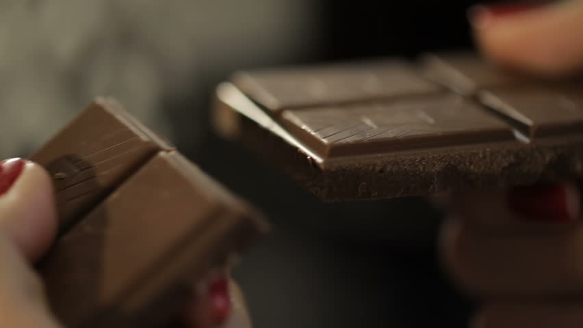 Woman breaks chocolate bar. Hands breaking, cracking dark milk chocolate. Person chef chocolatier snapping apart pieces of sweet chocolate for melting and making sweets desserts. Slow motion