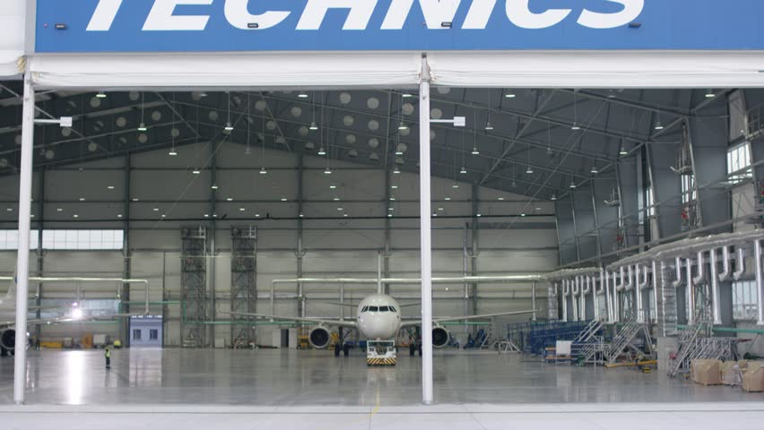 Roller shutter door and concrete floor of airport hangar and airplane background. Airport hangar from the outside with big tall doors. Front view. Aircraft Hangar