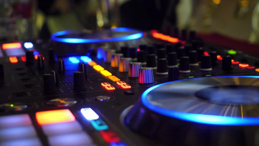 Close up of dj playing party music on modern cd usb player in disco club - Nightlife and entertainment concept. DJ turntable console mixer controlling with two hand in concert nightclub stage