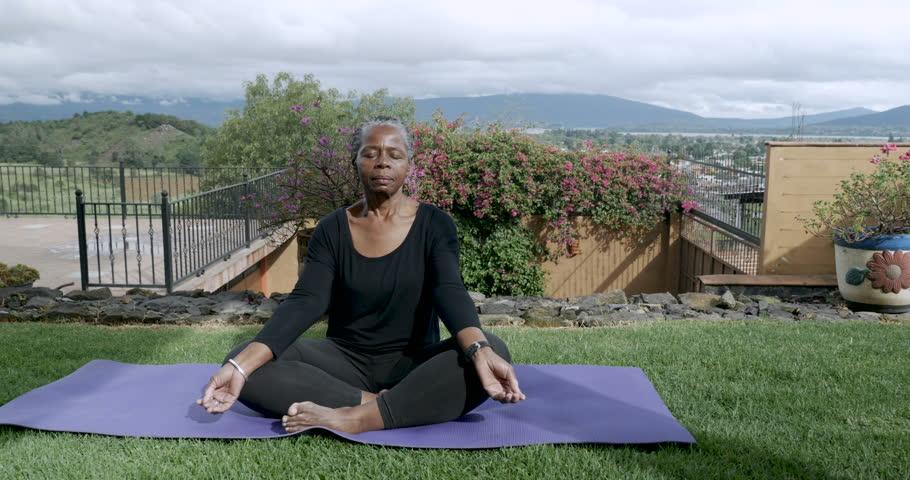 Healthy African American senior in 60s sitting cross legged meditating outside on a yoga mat - dolly shot   Shutterstock HD Video #33959050