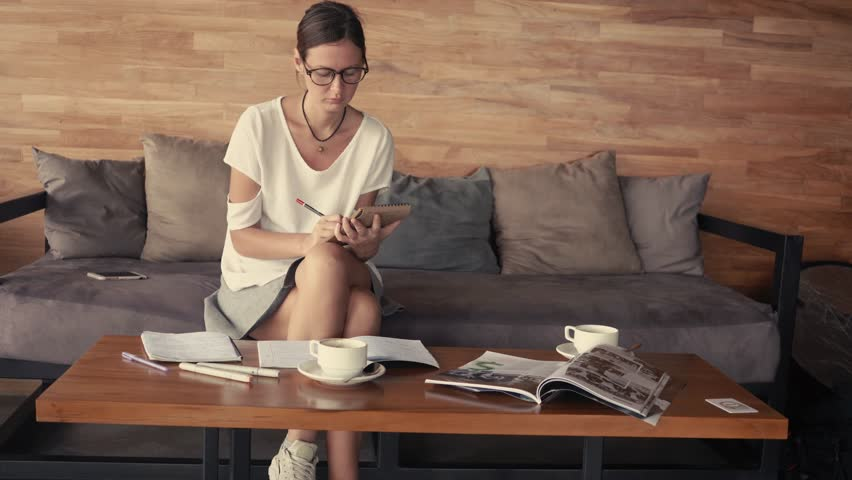 Young woman in glasses portrait sitting in cafe and drawing in notepad. Drinking coffee. Outdoor working concept. Coffee-house space in sunny loft | Shutterstock HD Video #33960223