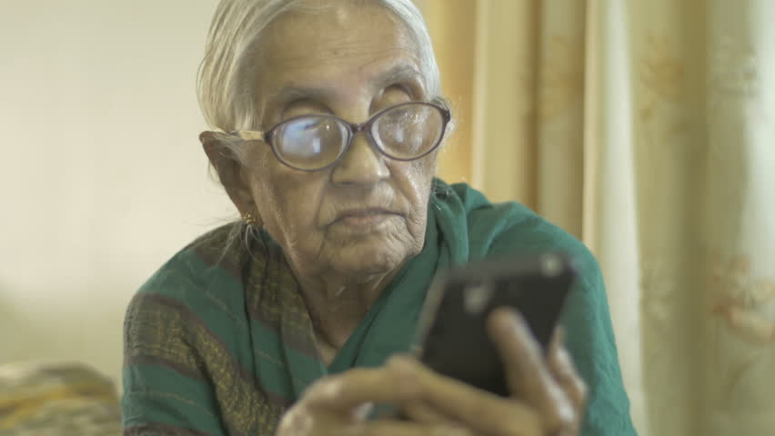 A very old 90 years retired Indian woman in  traditional attire - saree- using a smart phone