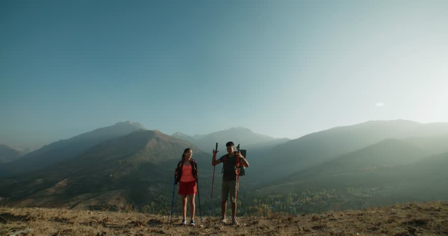 Asian couple on top of the mountain to raise his hands up, a symbol of success | Shutterstock HD Video #33977719