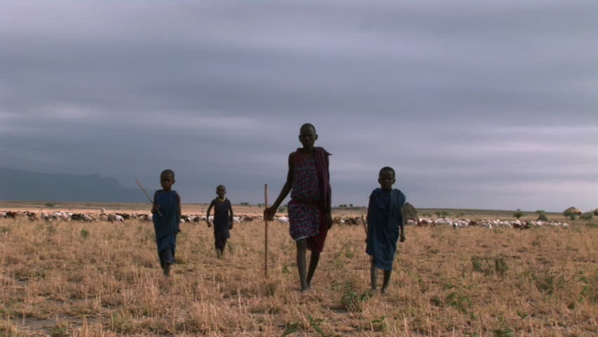 African brother and sister deprived children in a village walk towards camera. Storm sky.