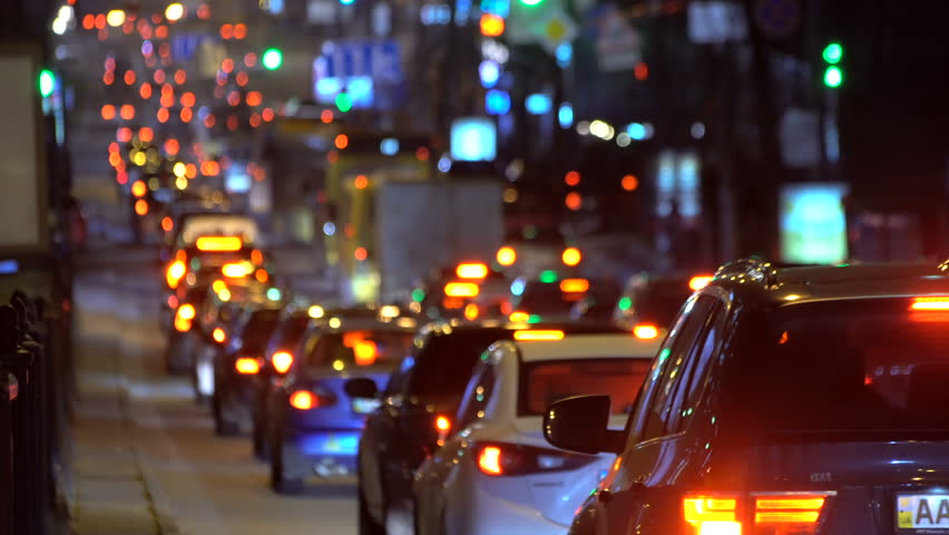 Car traffic jam at a busy avenue at night. Shot is taken on a long-focus lens