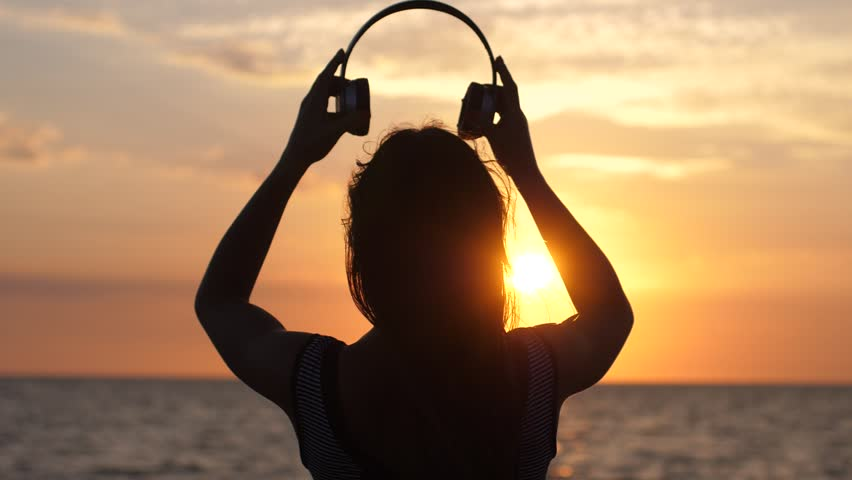 Silhouette of young woman wearing headphones have fun listening music on the beach at amazing sunset in slow motion. 1920x1080 #34017535