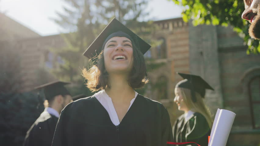 Young multi ethnical graduates in caps laughing out loud and having fun on their graduation day. Outdoors. Close up #34025368