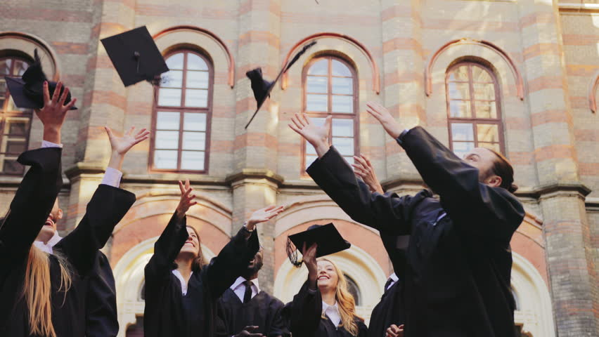 Group of multi ethnical graduates in traditional clothes tossing their caps up in the air happily in front of the University. Outdoors #34025413
