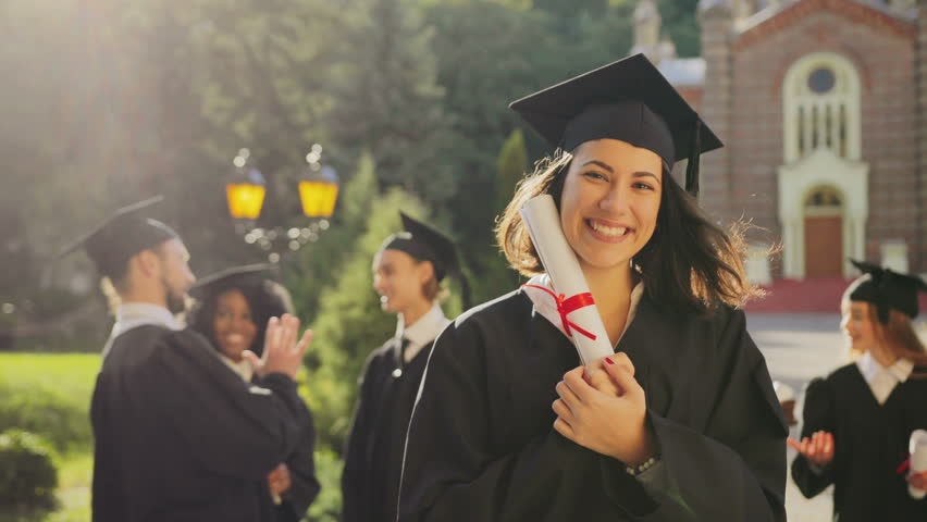 Portrait of the happy beautiful young female graduate in a traditional clothes and cap smiling to the camera and holding her diploma on a sunny day. Multi ethnical students on the background. Outside #34025422