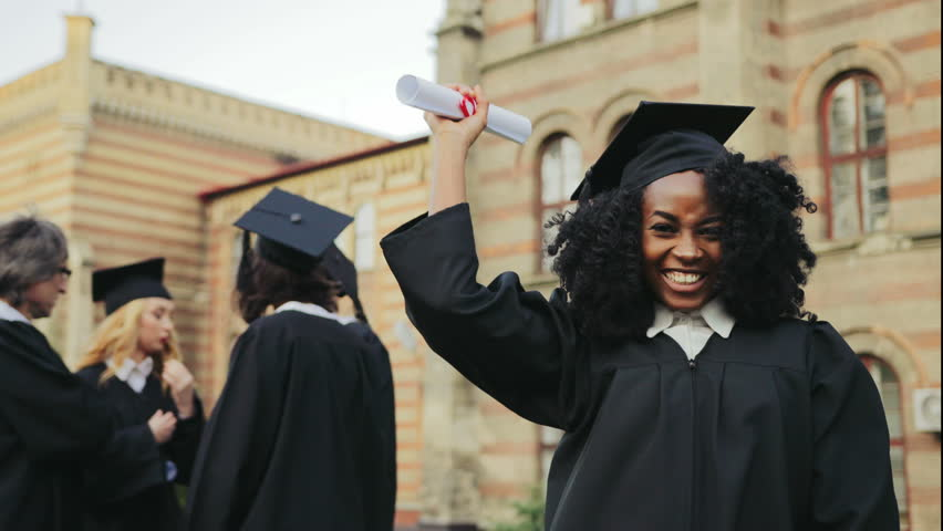 Portrait of the African American happy young graduated woman posing to the camera, showing her diploma and making YES gesture in front of the University. Graduates with professor on the background | Shutterstock HD Video #34025461