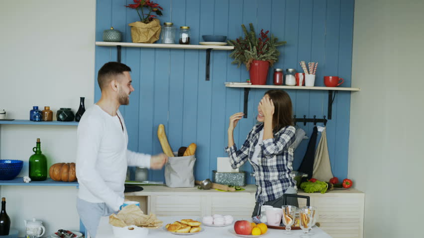 Young joyful couple have fun dancing and singing while set the table for breakfast in the kitchen at home #34031629