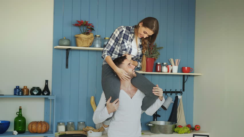 Happy young couple having fun in kitchen at home. Girl is sitting on boyfriend's neck #34031686