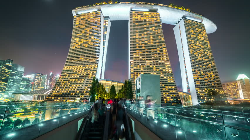 Timelapse People walk along the bridge to Marina Bay Sands at night in Singapore. August 2017