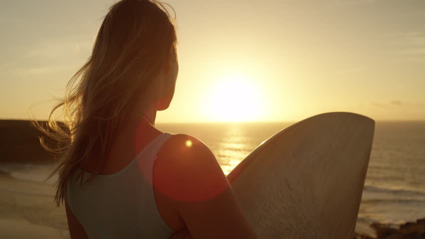 SLOW MOTION CLOSE UP: Surfer girl standing on rocky ocean cliff and watching breaking waves at golden sunset. Woman holding a surfboard, looking the waves at sunrise in Fuerteventura, Canary Islands | Shutterstock HD Video #34059553