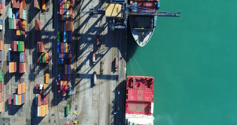 Aerial cinematic 4k footage Cargo freight ship with working crane bridge in shipyard for Logistic Import Export background , top view scene