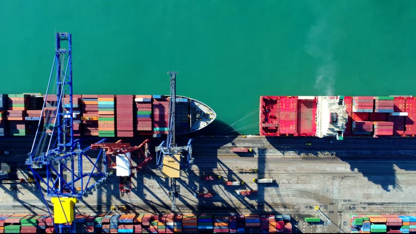 Aerial  4k UHD footage Cargo freight ship with working crane bridge in shipyard for Logistic Import Export background , top view