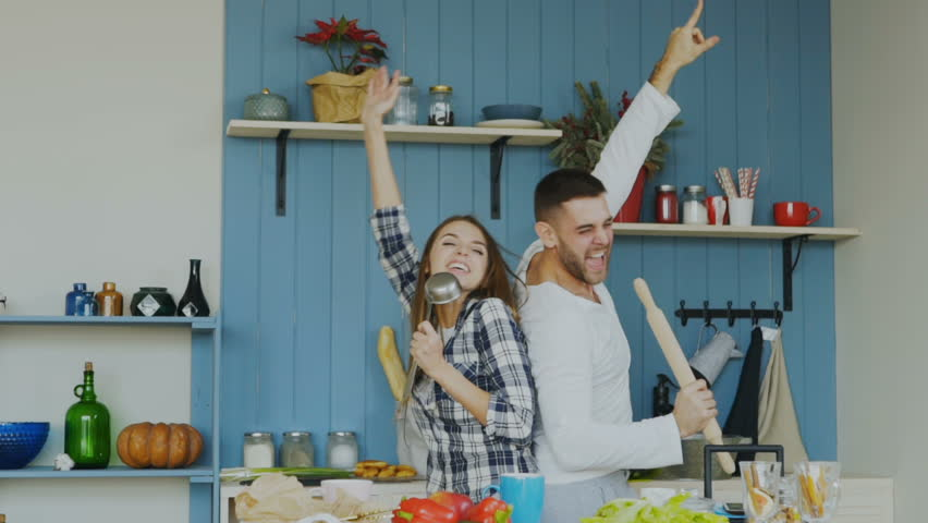 Slowmotion of Young joyful couple have fun dancing and singing while cooking in the kitchen at home Royalty-Free Stock Footage #34071550