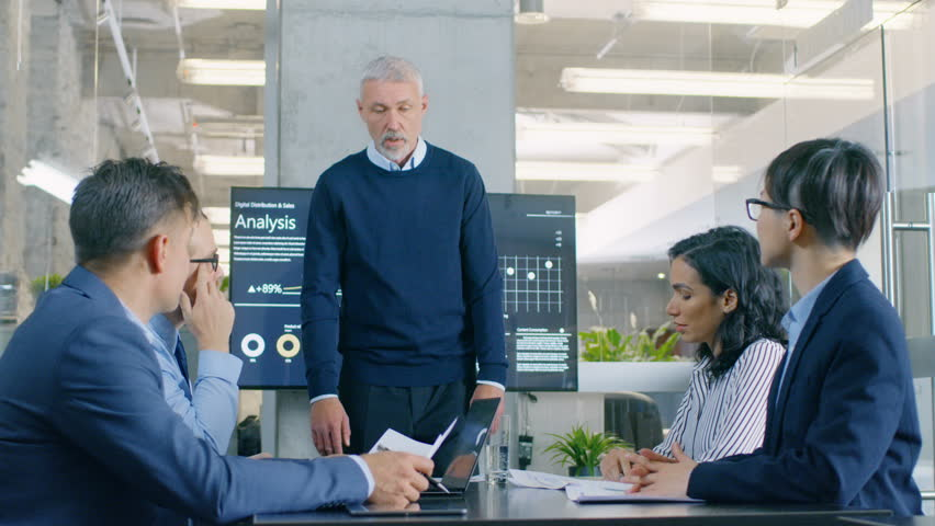 Senior Executive Explains Company's Vision and Potential to His Employees, Leans on the Table. They are Sitting at Big Table in Meeting Room. TV Screen on the Wall Shows Corporate Growth. 4K UHD. | Shutterstock HD Video #34080001