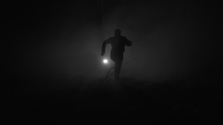 Silhouette of a man running in slow motion through the forest at winter night